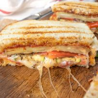 Grilled eggplant, zucchini bell pepper and cheese oozing from the panini