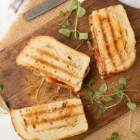 3 halves of a Grilled summer vegetable panini from above on a board with a knife and fresh herbs