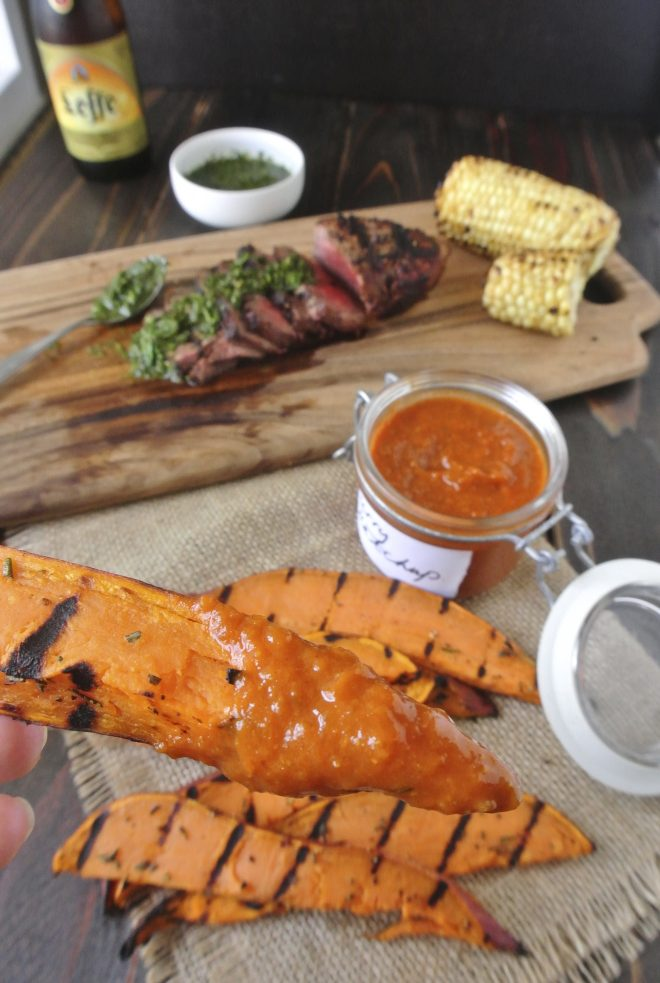A grilled sweet potato wedge dipping in curry ketchup