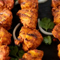 Perfectly grilled tandoori chicken on skewers