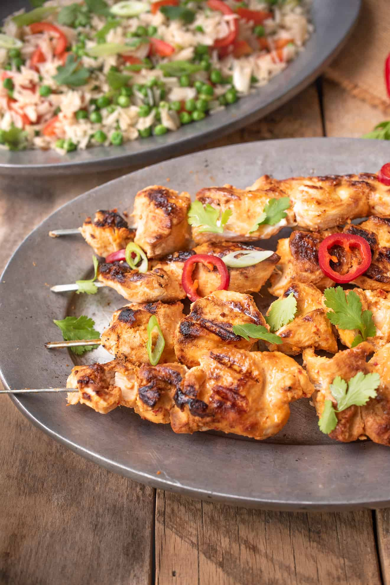 A closeup of Grilled Thai Chicken Kabob Skewers garnished with green onion and red peppers