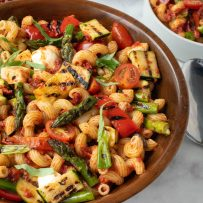 Colorful grilled vegetables in a wood bowl of pasta mixed with sun-dried tomato pesto