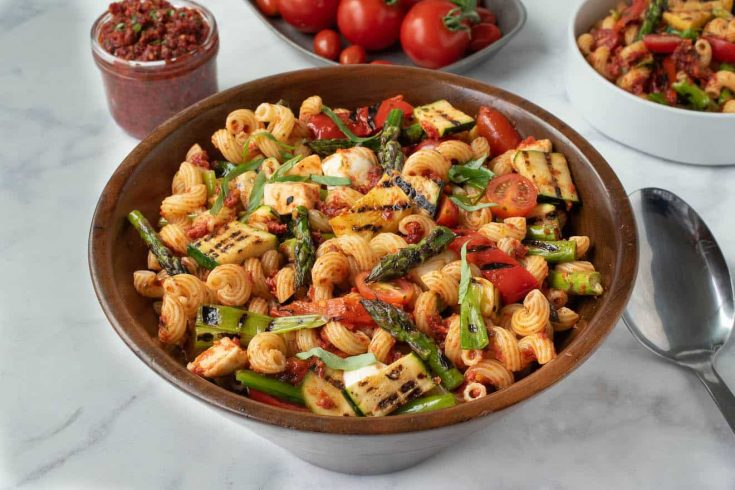 A large wood bowl filled with grilled vegetable sun-dried tomato pesto pasta with asparagus, red peppers, zucchini, spring onions and tomatoes