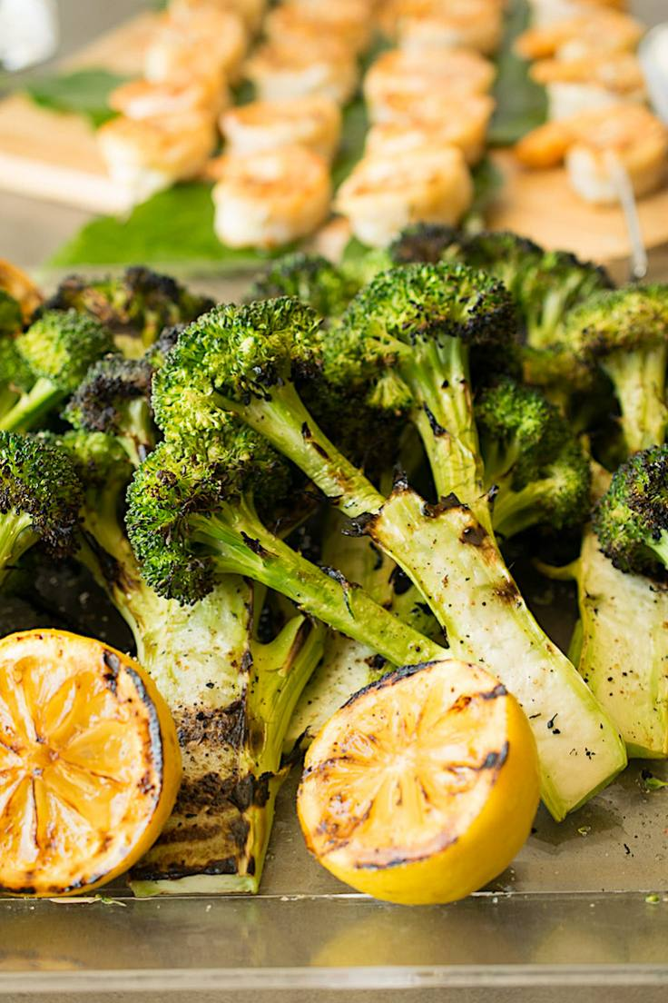 A tray of grilled broccoli with lemon and shrimp