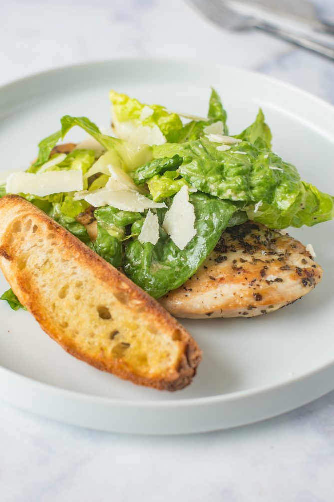 A large crouton with Caesar salad and a chicken breast on a white plate