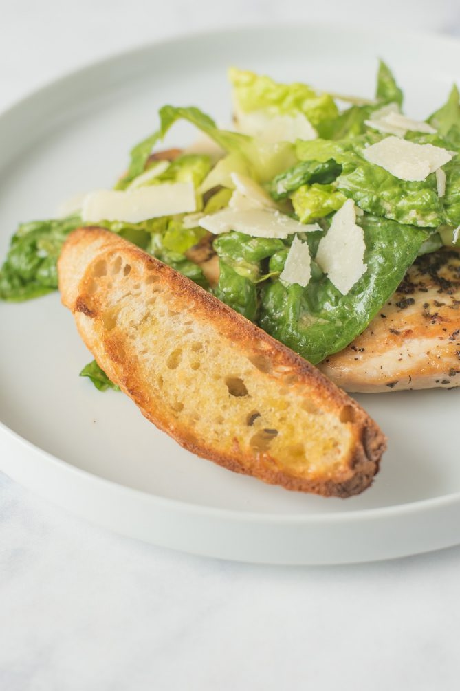 A large, toasted crouton propped up against lettuce with Parmesan and chicken