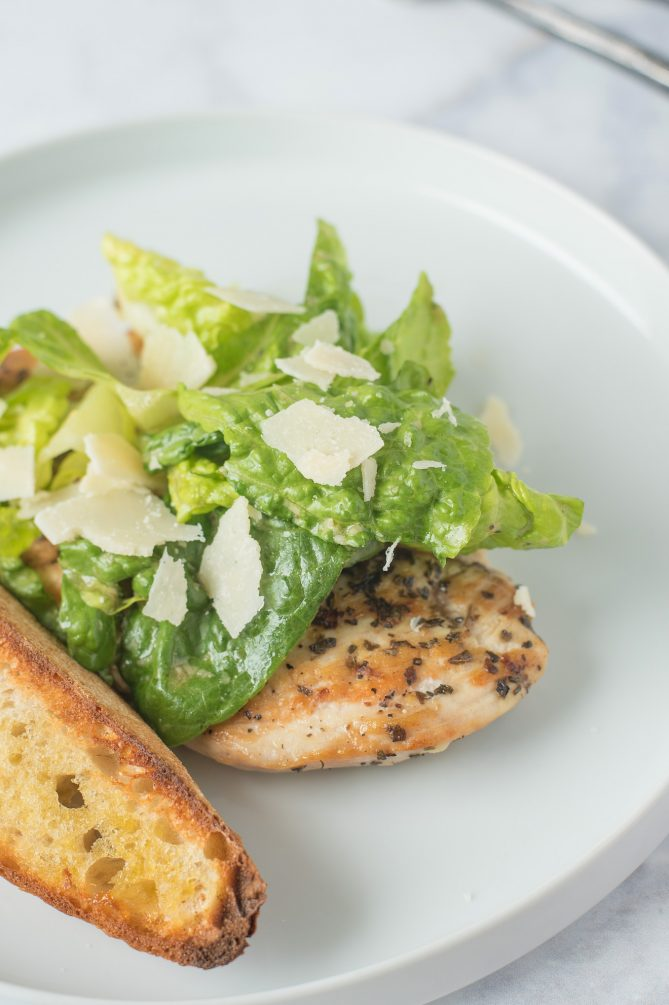 Shaved Parmesan on top of lettuce with a whole chicken breast and crusty bread