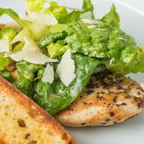 A chicken breast peeking out from under romaine lettuce topped with shaved Parmesan and a crouton