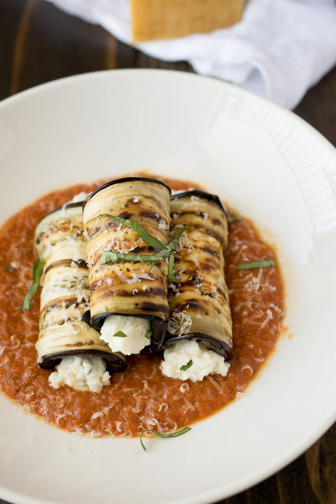 Grilled eggplant rollatini and marinara sauce in a white bowl