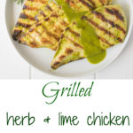 2 white plates of grilled chicken with herb sauce