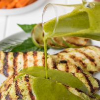 Chicken breasts with grill marks with herb sauce being poured over