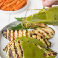 Pouring herb sauce over grilled chicken breasts