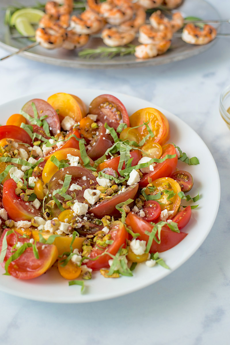 A white plate of colorful heirloom tomatoes with feta and pistachios  serves as the perfect side dish