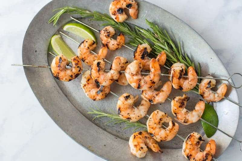 Skewers of grilled shrimp on a grey oval plate with fresh lime wedges and rosemary