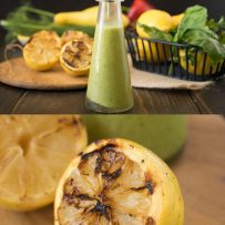 A bottle of salad dressing and a closeup of a grilled lemon cut in half