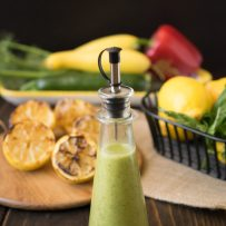 A salad dressing bottle filled with dressing with grilled lemons in the background