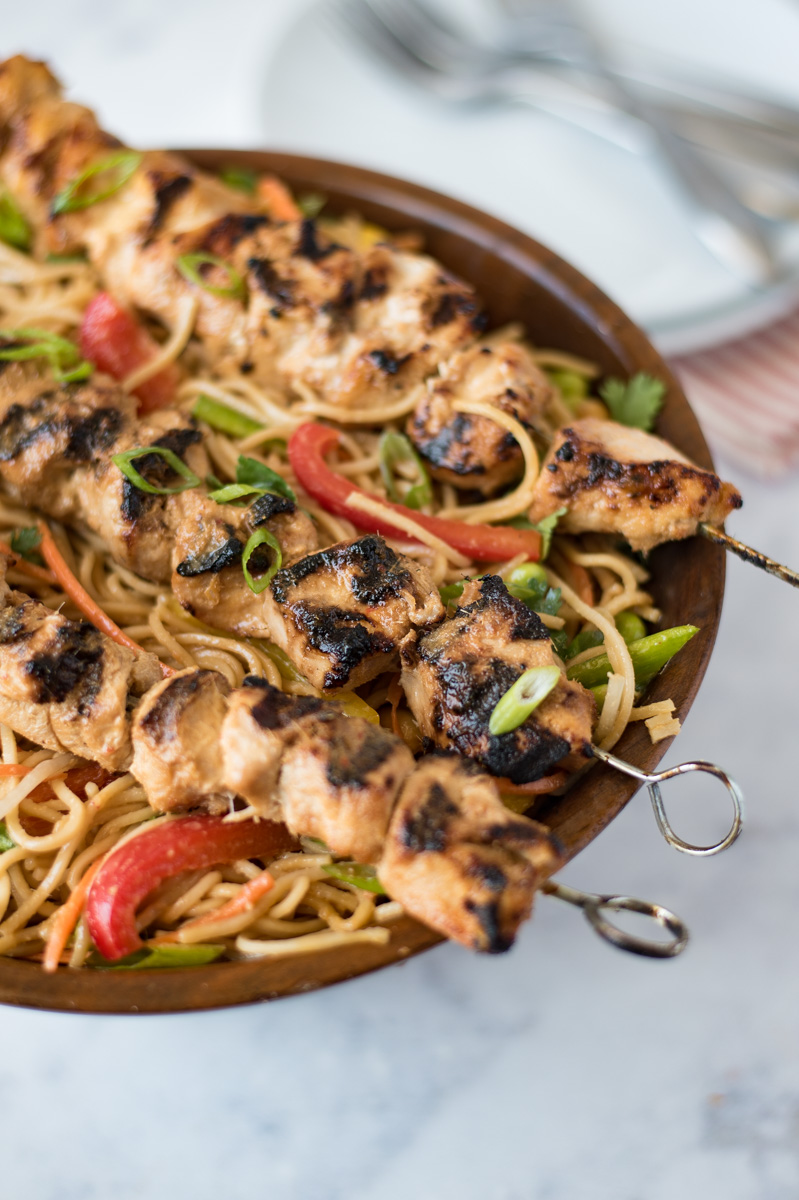 A large bowl of lemongrass noodle salad with lemongrass grilled chicken skewers laid across the top