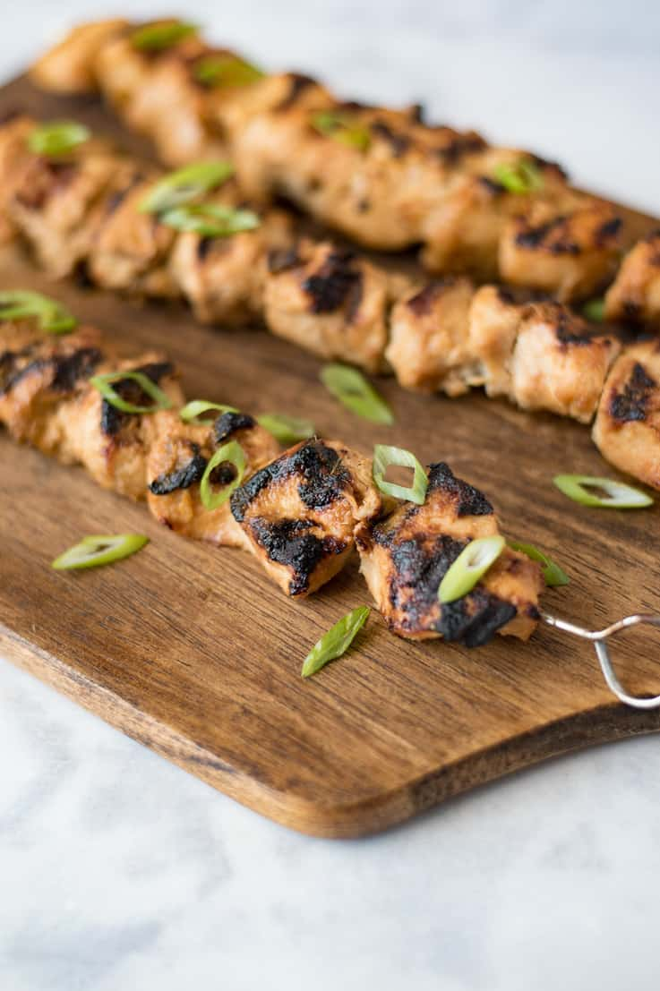 Grilled lemongrass chicken skewers on a serving board garnished with sliced scallions