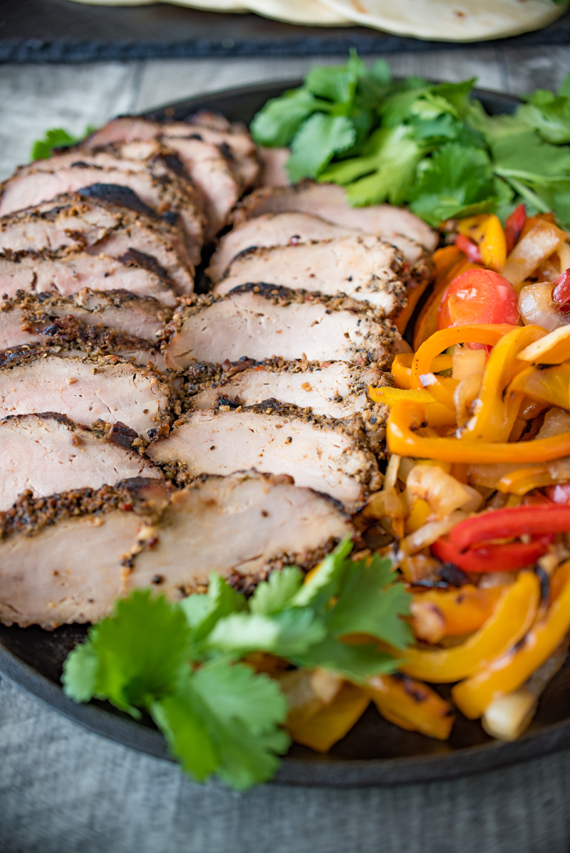 Grilled pork tenderloin fajitas are a quick and easy way to get a summer meal served in under 30 minutes. Marinated pork tenderloin is grilled along with onions and peppers. The pork is sliced then all are served on warm tortillas garnished with fresh avocado and cilantro.