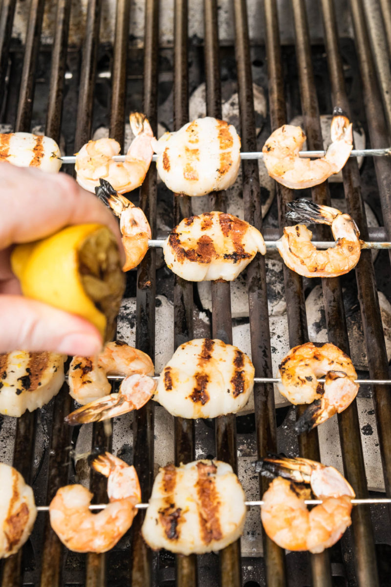 Skewered shrimp and scallops on a grill with fresh lemon being squeezed onto them