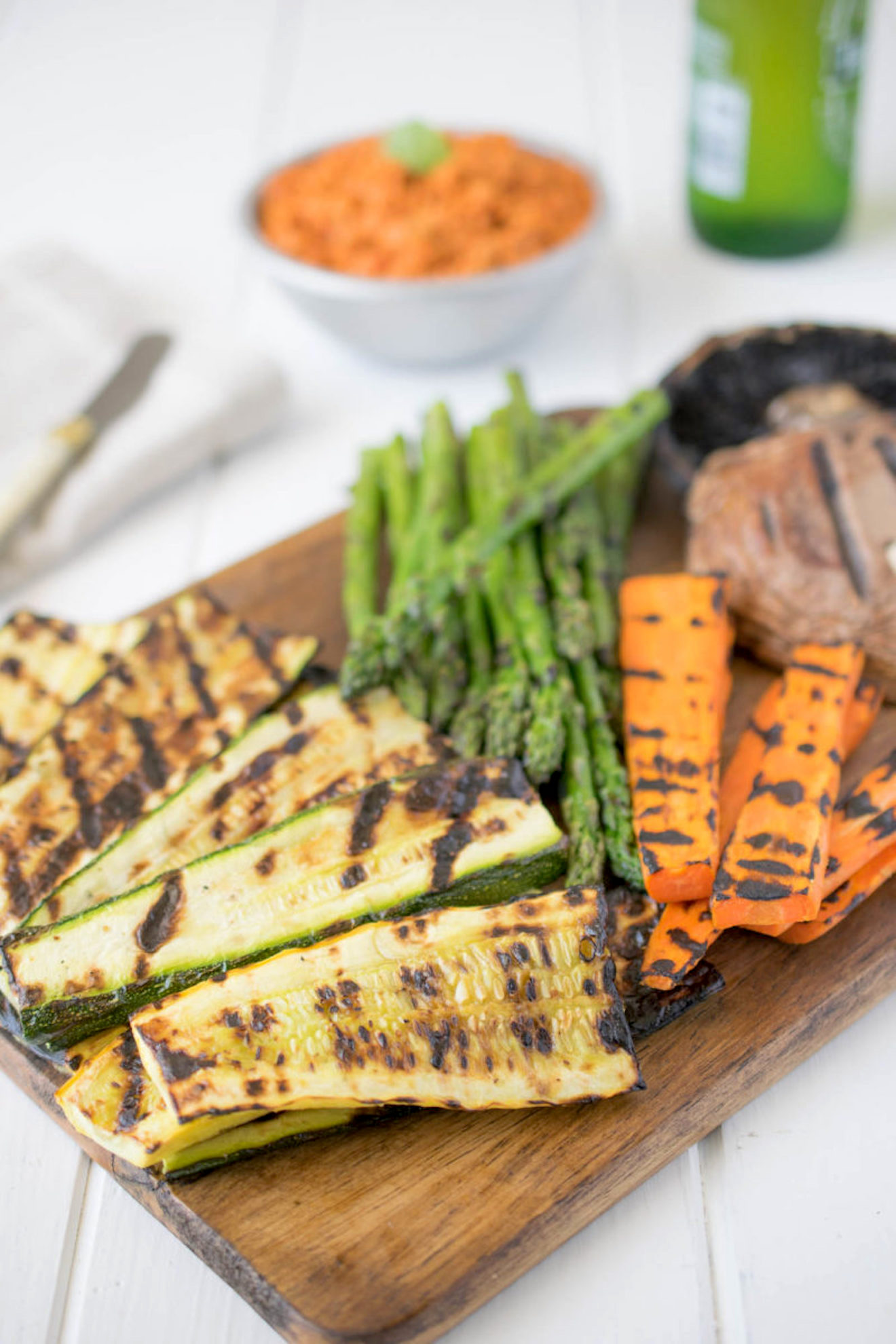 Grilled zucchini, carrots, asparagus and mushrooms on a serving board with sun-dried tomato dip