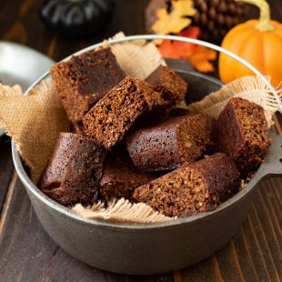 Squares of parkin cake are piled in a grey dish