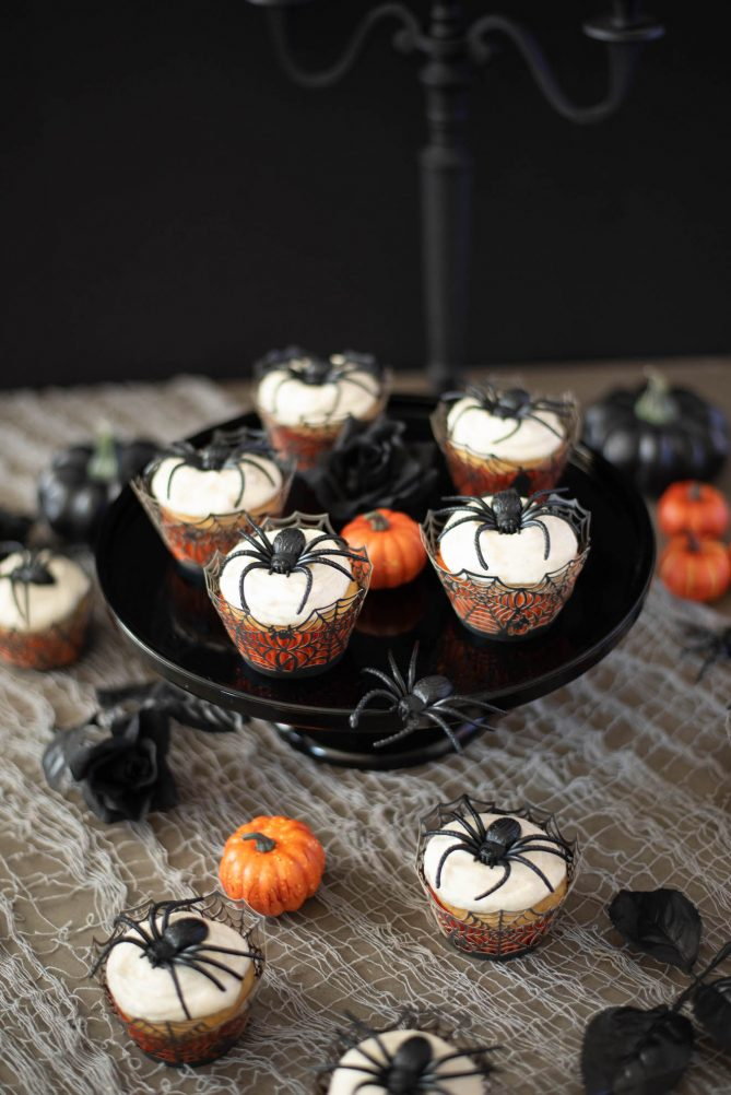 5 spider cupcakes on a black cake stand with some cupcakes underneath