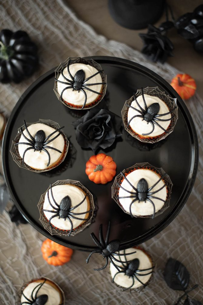 Plastic spiders on top of cupcakes viewed from overhead with black roses and a mini pumpkin