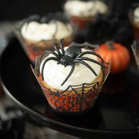A closeup of a cupcake in a spider web muffin cup topped with a large plastic spider with mini orange pumpkins around