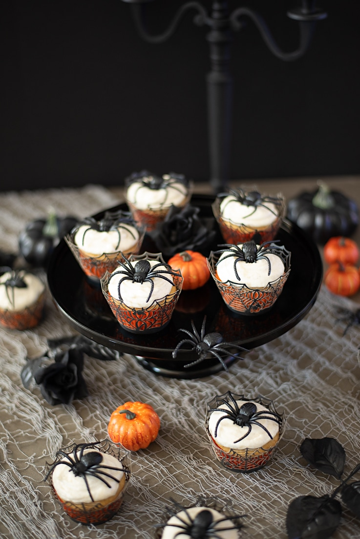A selection of Halloween Pumpkin Spiced Applesauce Spider Cupcakes on a black cake stand with mini orange pumpkins and fake spiders