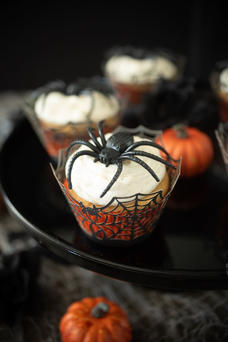 Pumpkin spiced applesauce cupcake in an orange liner wrapped in a spiderweb liner with cream cheese frosting and a plastic spider