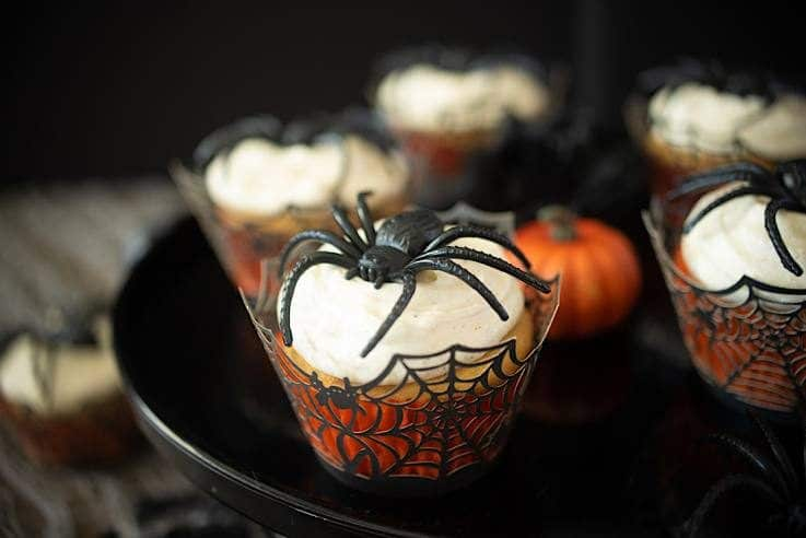 A closeup showing the spiderweb cupcake liner, creamy frosting and large spider decoration