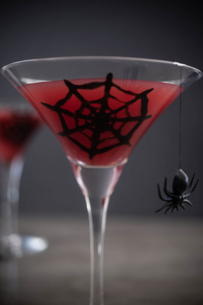 A closeup of a glass with a black spider web painted on the inside that has red liquid inside and a plastic spider hanging