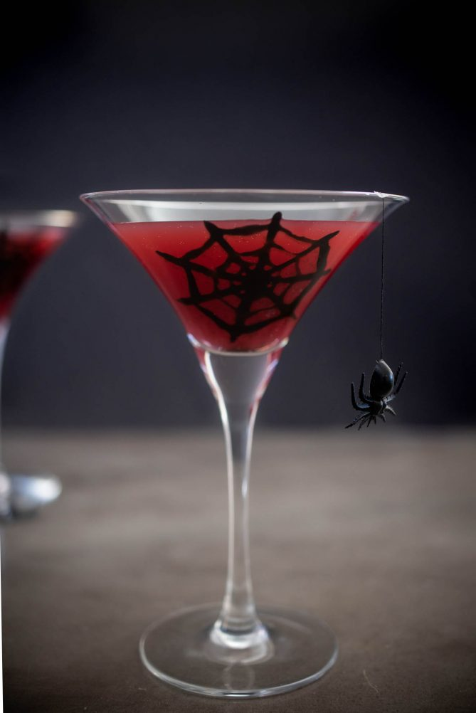 A spooky Halloween drink of a blood orange martini with a spider web and spider on the glass