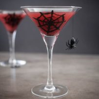 2 martini stemmed glasses with blood orange juice decorated with a spider web and spider