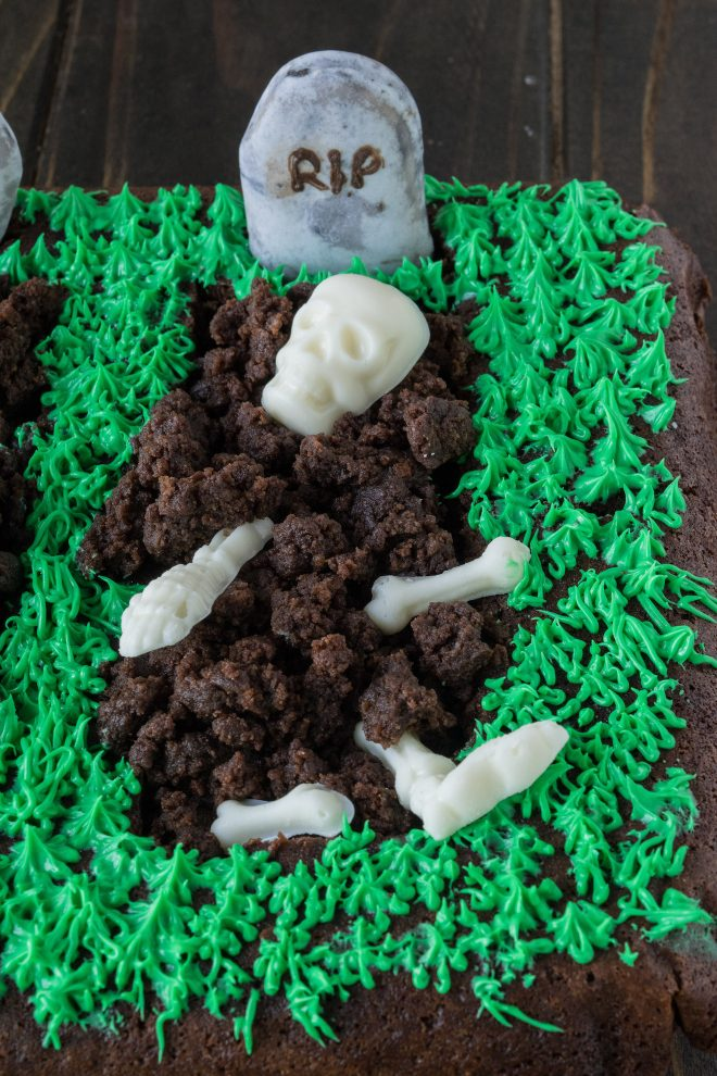A graveyard made from brownie with a white chocolate skeleton and green frosting grass