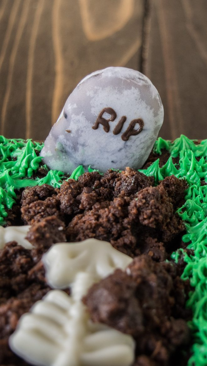 A closeup of the cookie headstone with RIP piped in chocolate