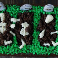 3 graves cut out of a brownie with white chocolate skeletons buried