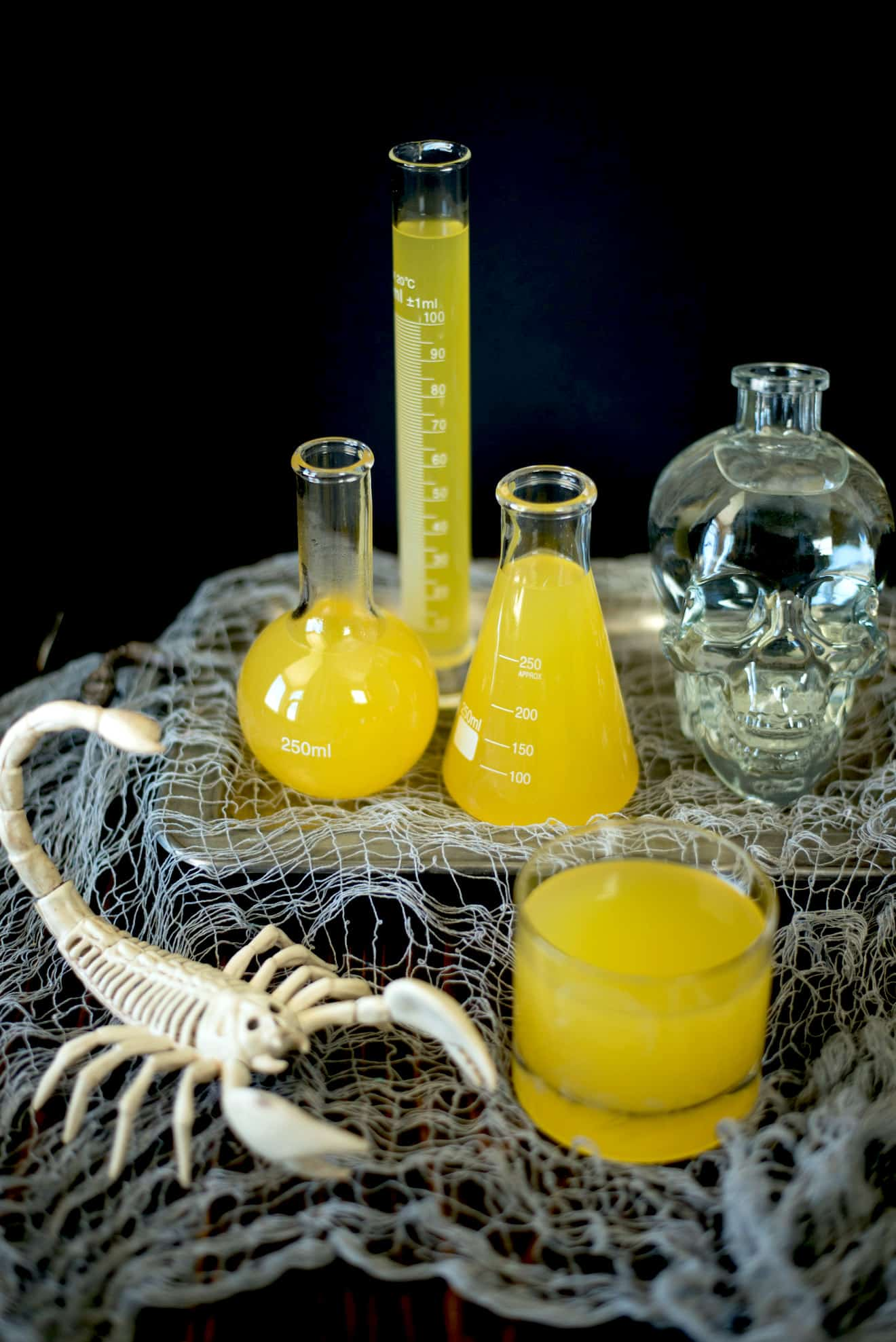 A skeleton scorpion with Halloween Scorpion Venom punch and a bottle of skull vodka