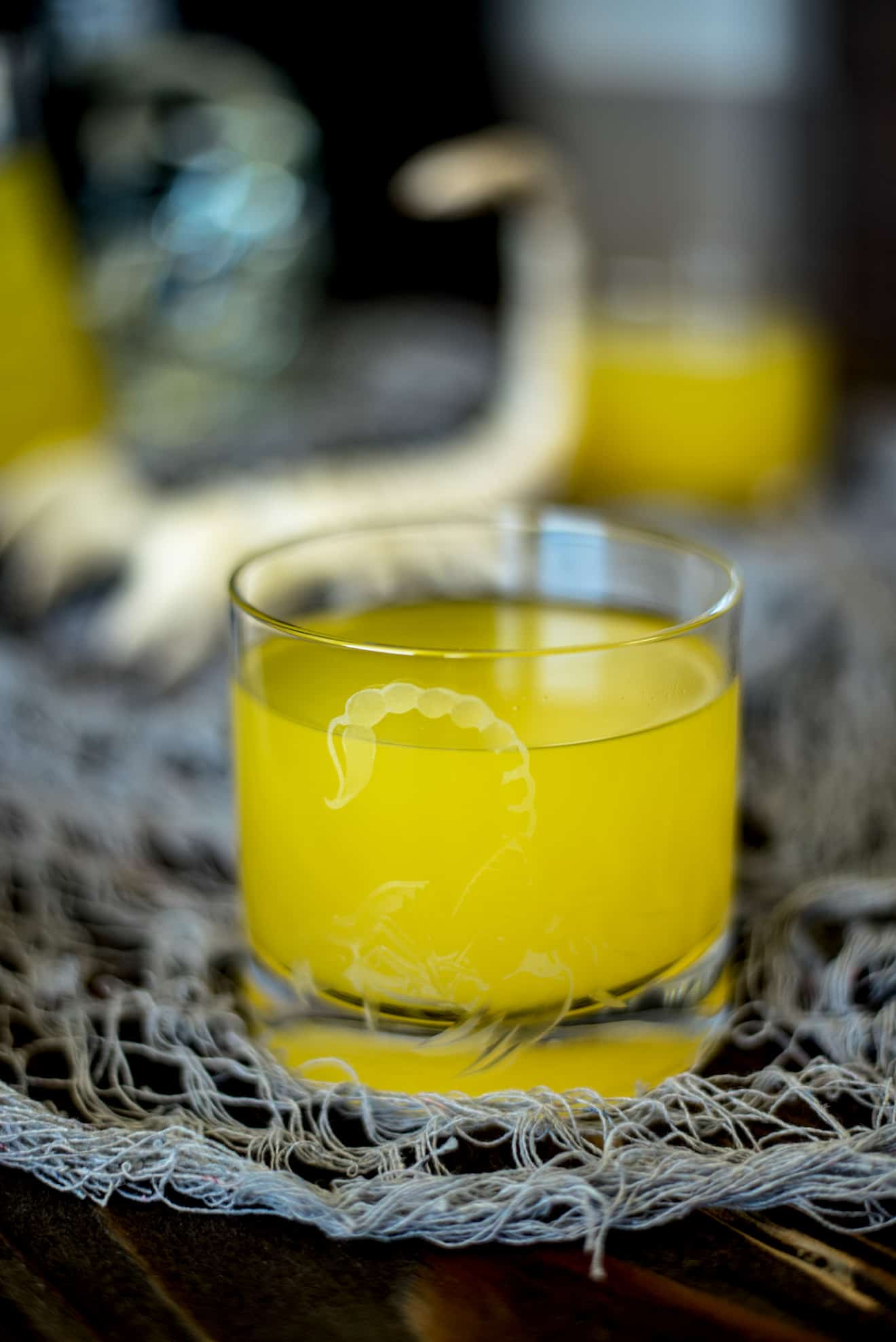 A scorpion glass filled bright yellow with Halloween Scorpion Venom Punch