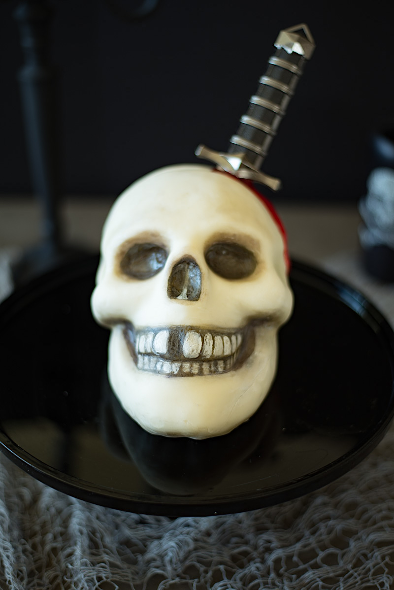 A skull cake covered in white fondant and painted with food paint with a real dagger and red blood