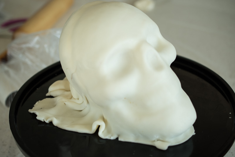 A skull cake being made, covered in white fondant