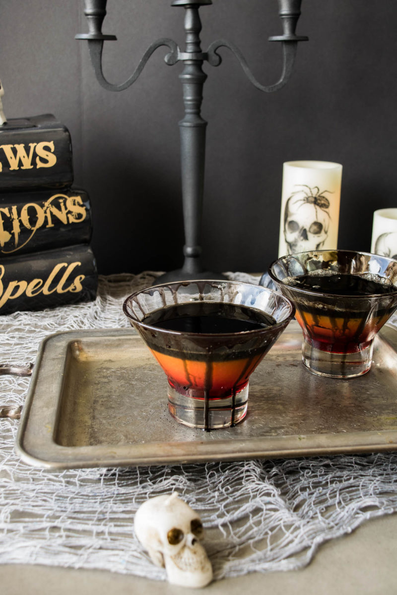 A spooky drinks display on a silver tray with skulls and black candelabra
