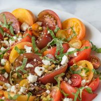 A colorful display of large and small tomatoes that are sliced and served with feta cheese, pistachios and basil