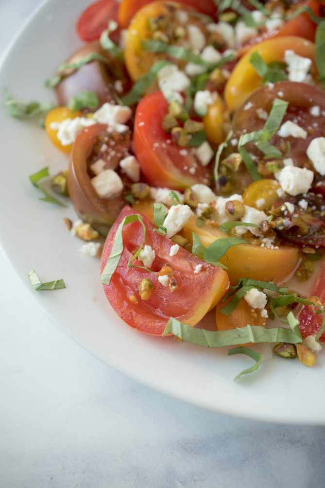 A closeup of a juicy, red and yellow heirloom tomato with chopped basil, feta and pistachios