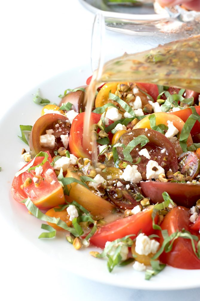 Pouring dressing onto a platter of sliced tomatoes with pistachios, feta and fresh basil