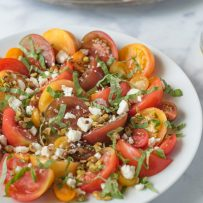 Slices of different color heirloom tomatoes, large and small on a plate topped with crumbled feta cheese, toasted pistachios and basil
