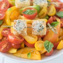 2 Parmesan basil croutons on a skewer on top of tomato salad