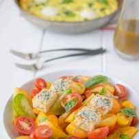 Red and yellow heirloom tomatoes in a bowl topped with Parmesan basil croutons