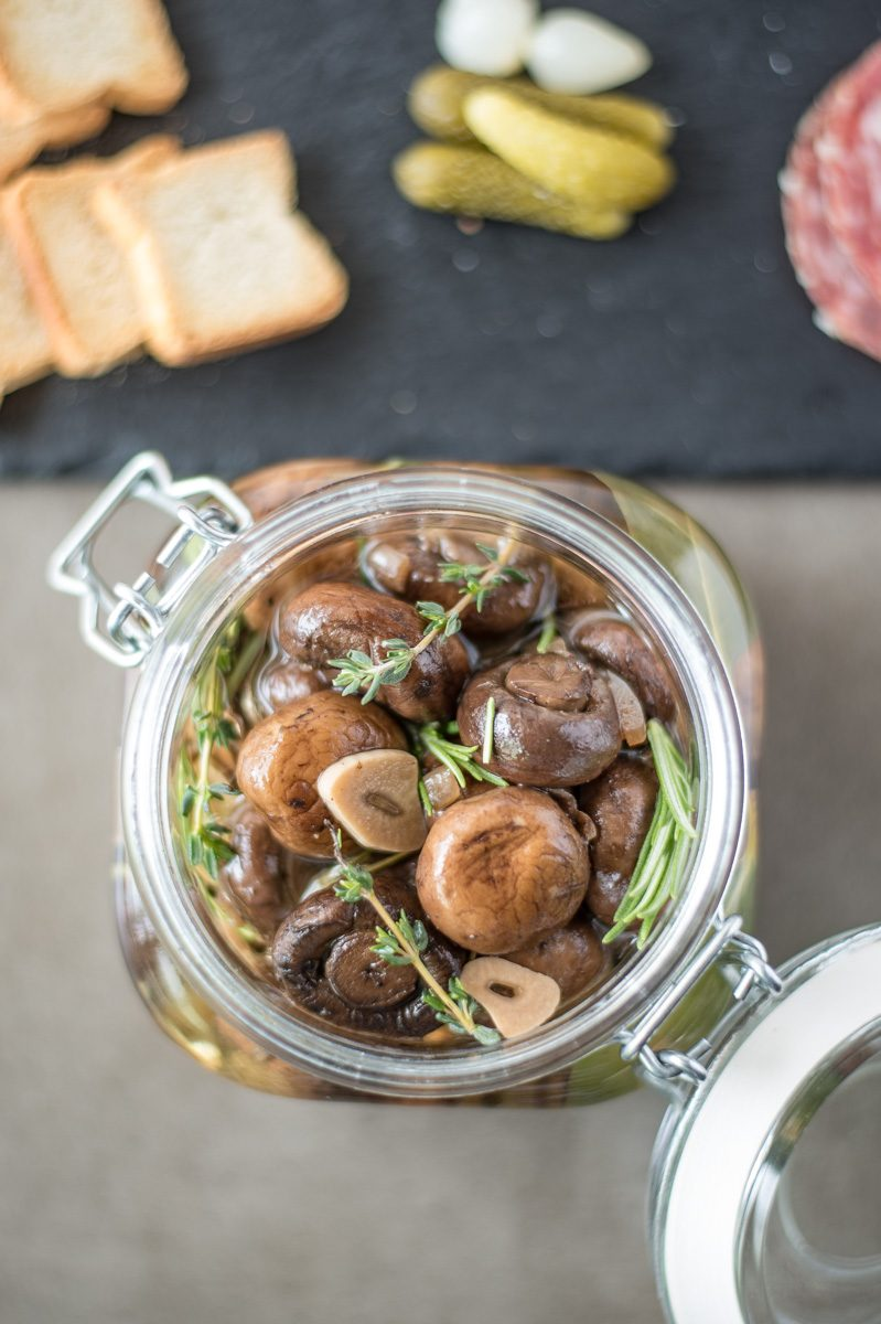Herb and garlic marinated mushrooms from overhead in a jar